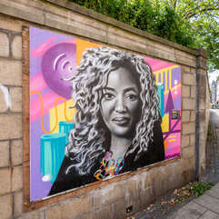 Black and white portrait of Dr. Anne-Marie Imafidon against a colorful background mounted along a brick wall