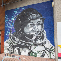 Black and white portrait of Helen Sharman in her space suit with a sketch of the MIR Space Station in the background painted on the wall of the Citadel Youth Centre