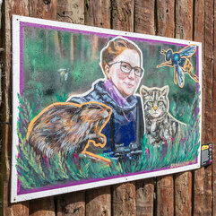 Portrait of Dr. Helen Senn surrounded by a beaver, wildcat, and wasp displayed near the wildcat enclosure at Edinburgh Zoo