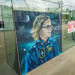 Portrait of Dr. Kathy Sullivan in her flight suit with a background that merges space and the ocean displayed at the entrance of Dynamic Earth