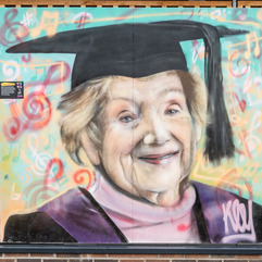 Portrait of Lorna Prendergast in her graduate cap and gown with a background of musical notations